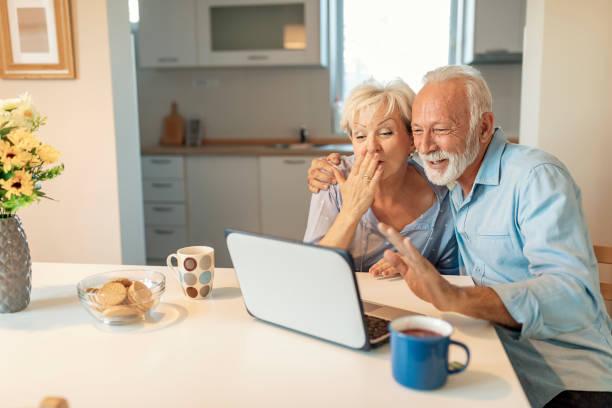 Couples aînés appréciant une session de chat vidéo avec leur famille - Photo