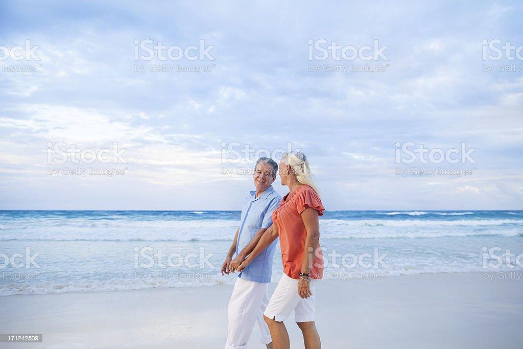 Senior couple enjoying a walk on the beach royalty-free stock photo