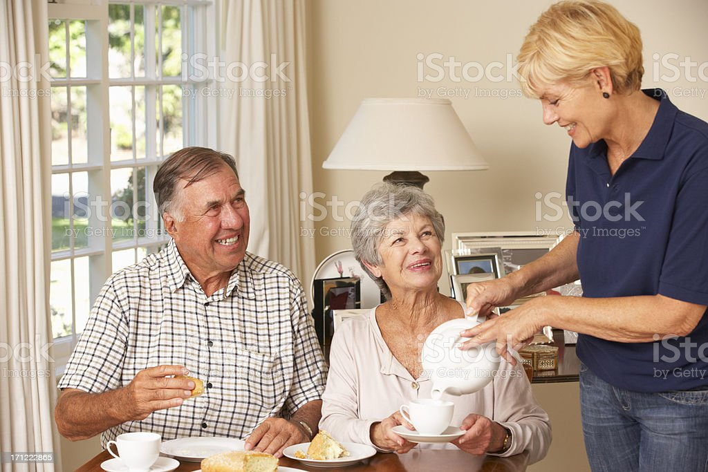 Senior Couple Enjoying Afternoon Tea Together At Home With Carer royalty-free stock photo