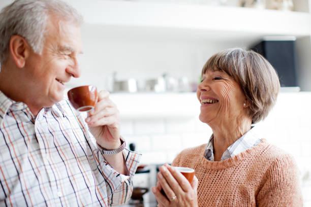 Senior couple enjoying an espresso in the kitchen stock photo