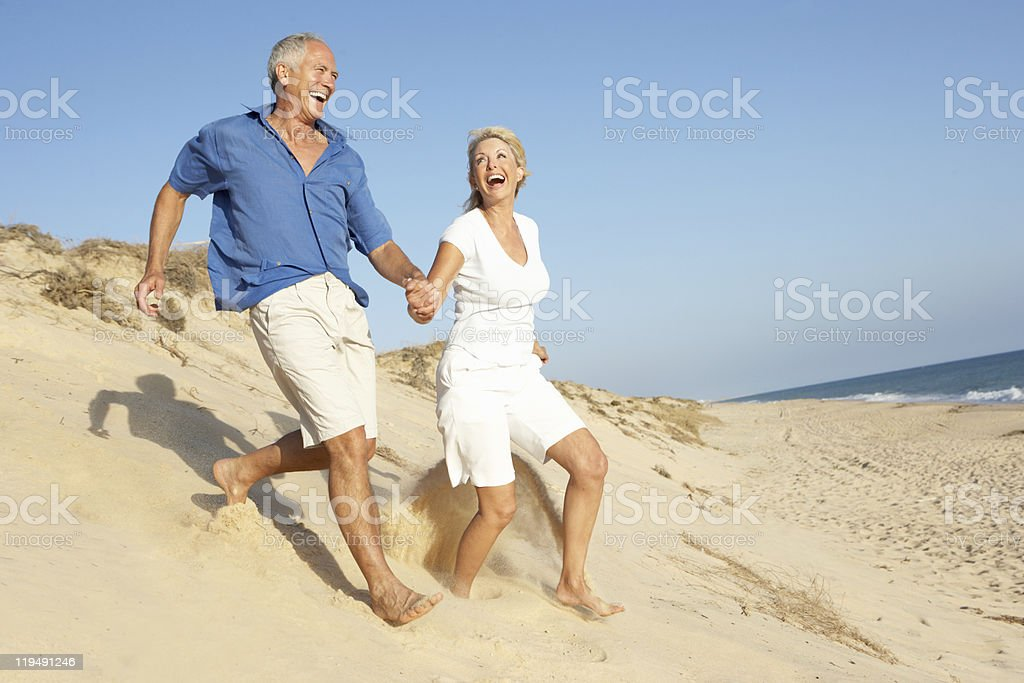 Senior Couple Enjoying Beach Holiday Running Down Sand Dune stock photo
