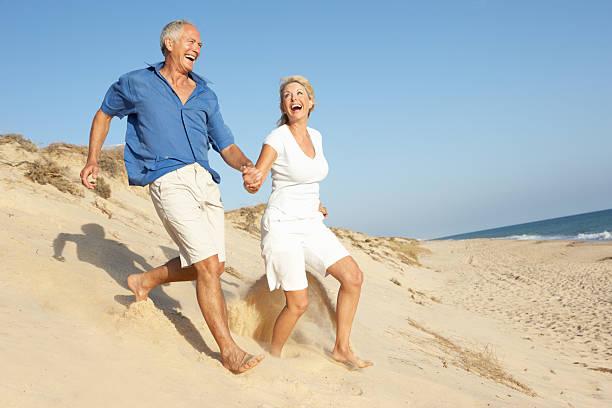 Senior Couple Enjoying Beach Holiday Running Down Sand Dune stock photo