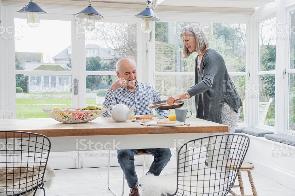 Senior couple enjoying breakfast at the dinner table stock photo
