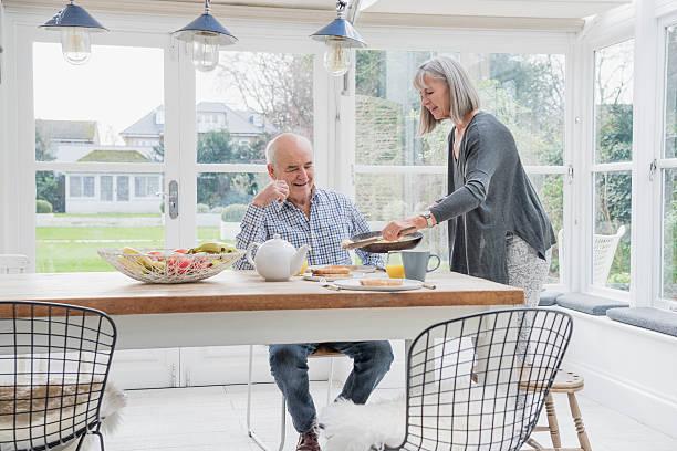 пожилая пара наслаждаясь завтрак в обеденным столом - оранжерея стоковые фото и изображения