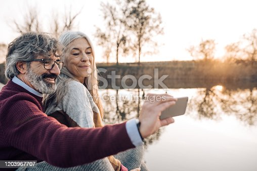 Senior couple enjoying on the river dock after hiking and taking a selfie.
