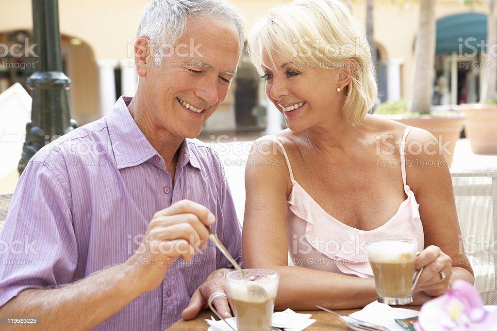 Senior Couple Enjoying Coffee And Cake In Café royalty-free stock photo