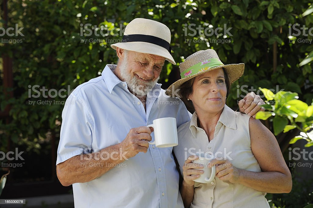 Senior couple enjoying coffee in garden stock photo