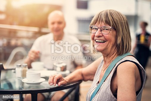 Senior couple enjoying coffee in hotel resort outdoors restaurant. The woman is smiling at the camera.