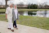 Senior couple enjoying day and taking a walk on footpath near pond
