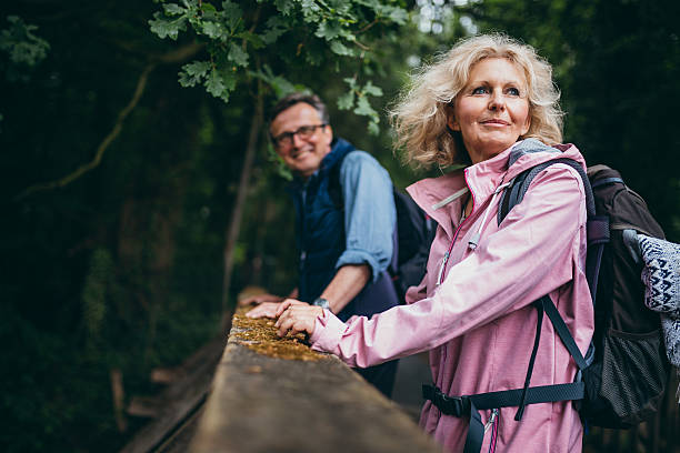 senior couple enjoying hike in the forest - hiking stock photos and pictures