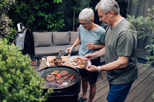 Senior couple preparing barbecue for the whole family at the backyard.