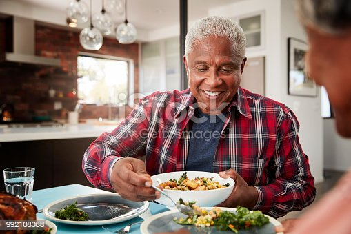 istock Senior Couple Enjoying Meal Around Table At Home 992108088