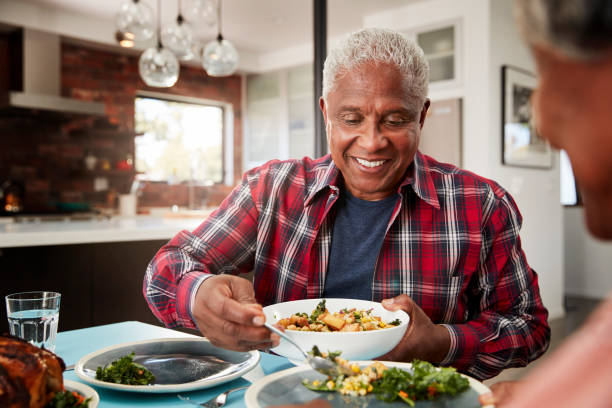 Senior Couple Enjoying Meal Around Table At Home Senior Couple Enjoying Meal Around Table At Home eating stock pictures, royalty-free photos & images