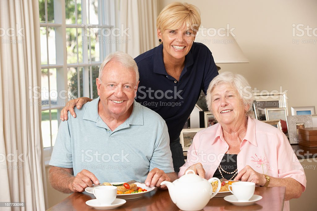 Senior Couple Enjoying Meal Together With Home Help royalty-free stock photo