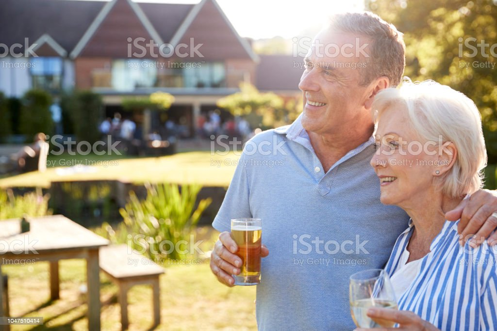 Senior Couple Enjoying Outdoor Summer Drink At Pub стоковое фото