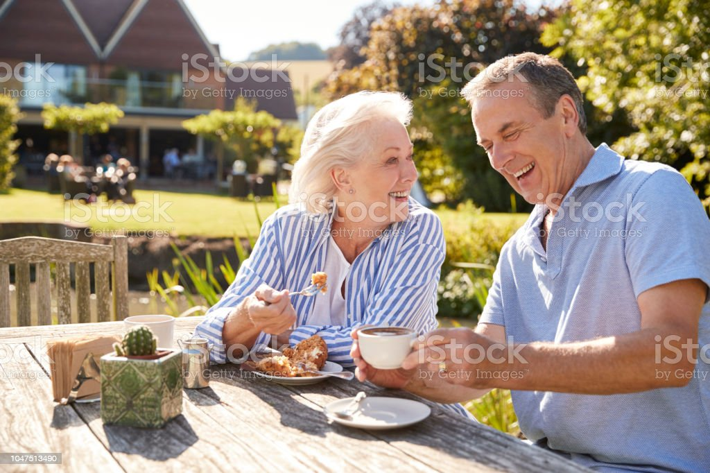 Senior Couple Enjoying Outdoor Summer Snack At Cafe стоковое фото