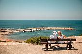 Senior couple sitting down on a bench overlooking the Mediterranean Sea. They are relaxing and spending time together.