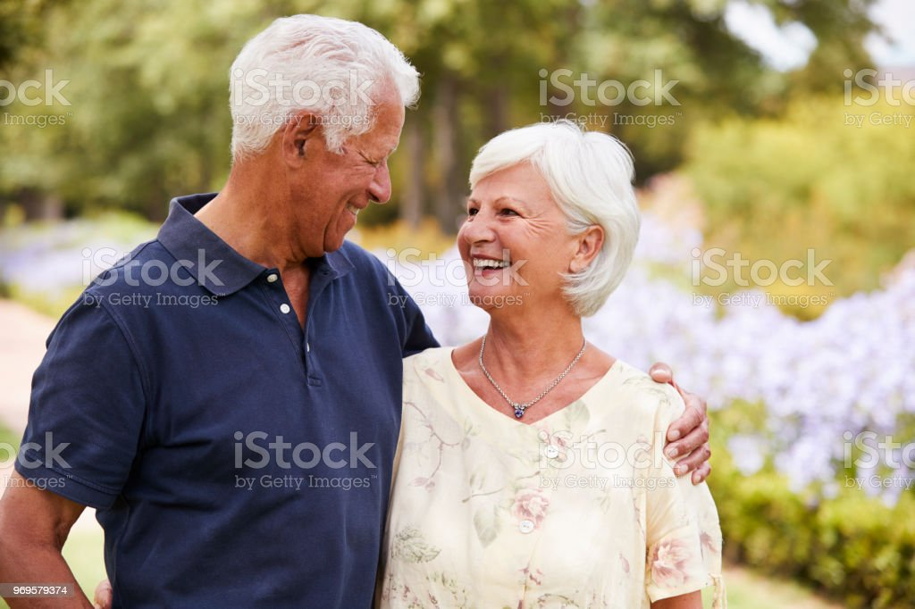 Senior Couple Enjoying Walk In Park Together стоковое фото