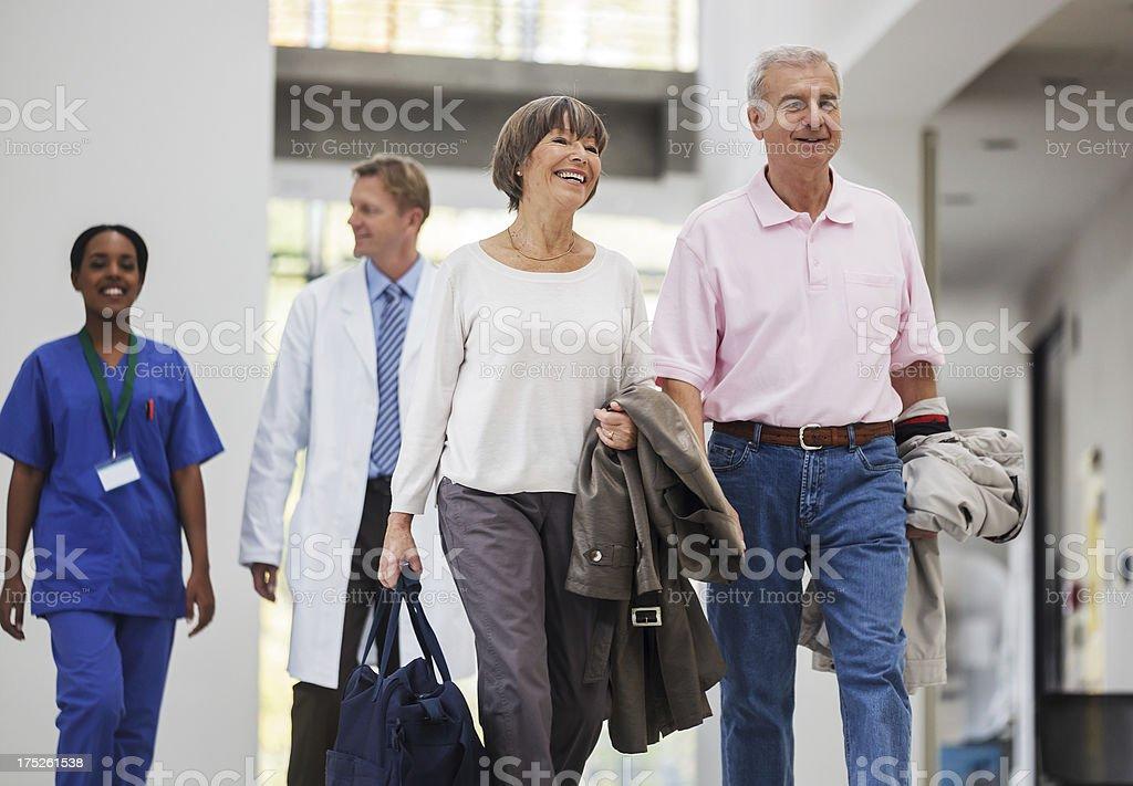 Senior Couple entering Hospital Senior couple entering the hospital with doctors walking behind them. horizontal shot. 70-79 Years Stock Photo