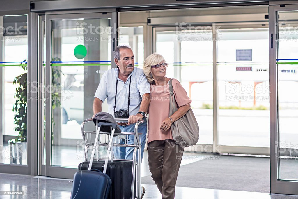 Senior couple entering with suitcase to the airport stock photo