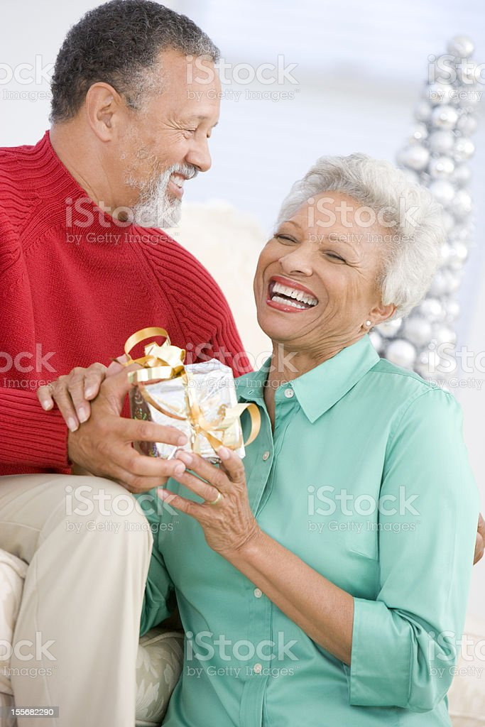 Senior Couple Exchanging A Christmas Gift stock photo
