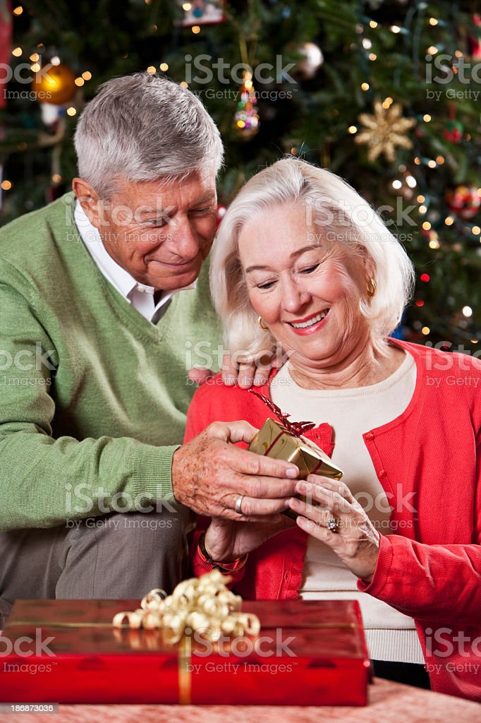 Senior couple exchanging Christmas gifts in front of tree. royalty-free stock photo