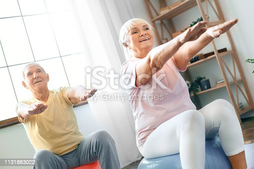 Senior man and woman together indoors sitting on exercise ball doing aerobics hands in front smiling