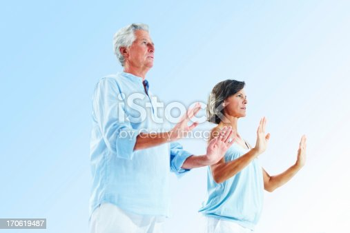 Senior couple exercising against blue background