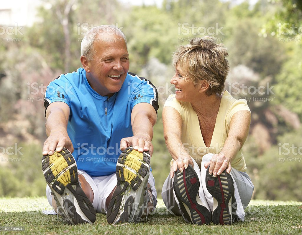 Senior couple exercising together in park stock photo