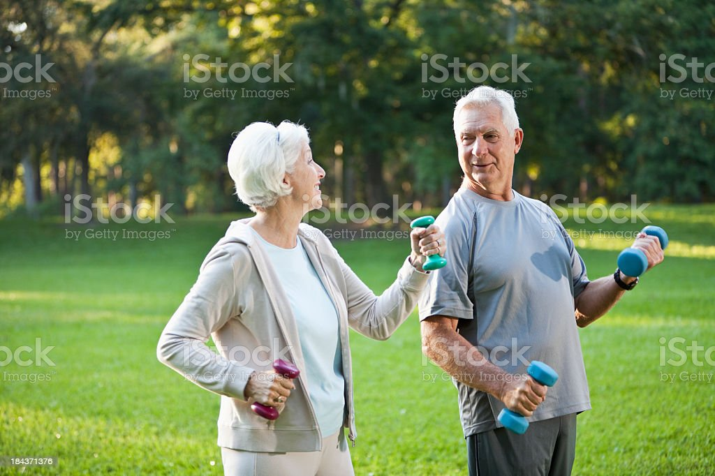 Senior couple exercising together outdoors stock photo