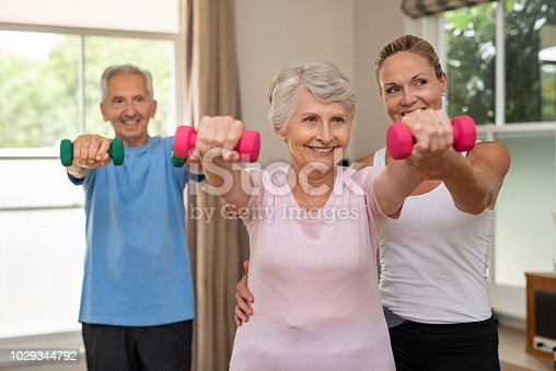 istock Senior couple exercising using dumbbells 1029344792