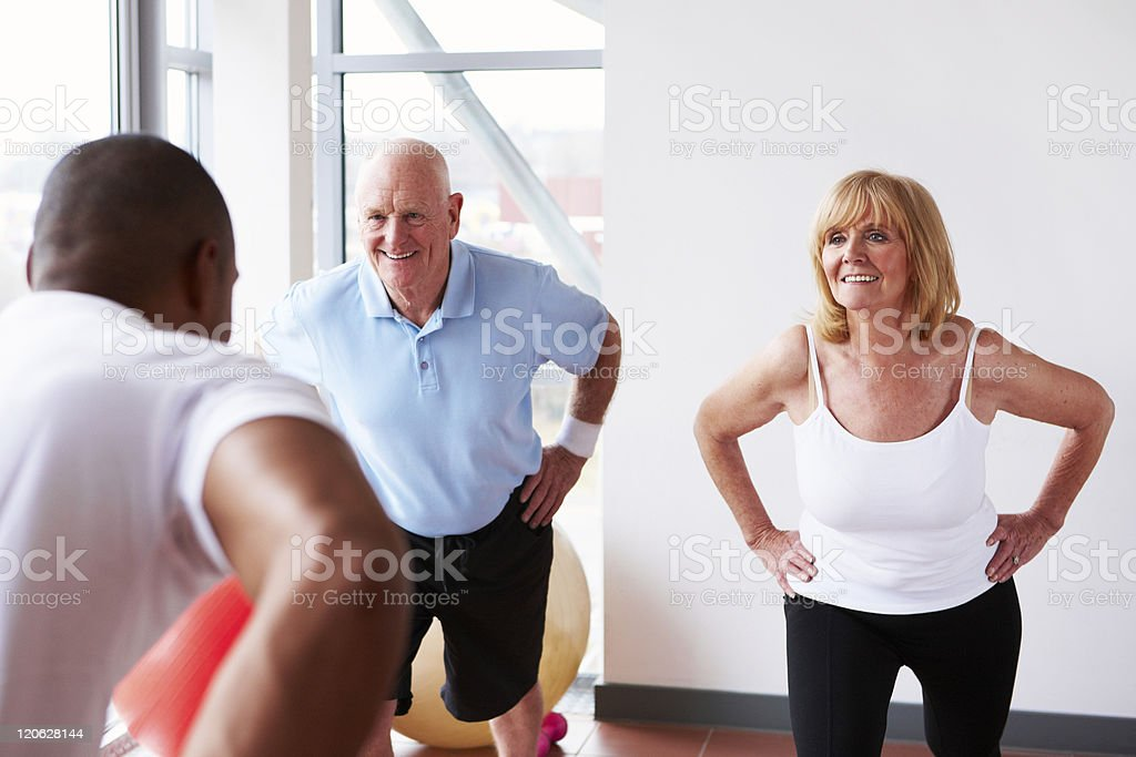 Senior Couple Exercising with a Trainer royalty-free stock photo