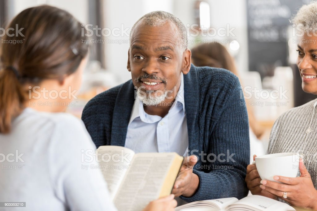 A senior couple explain Bible passage to young woman stock photo