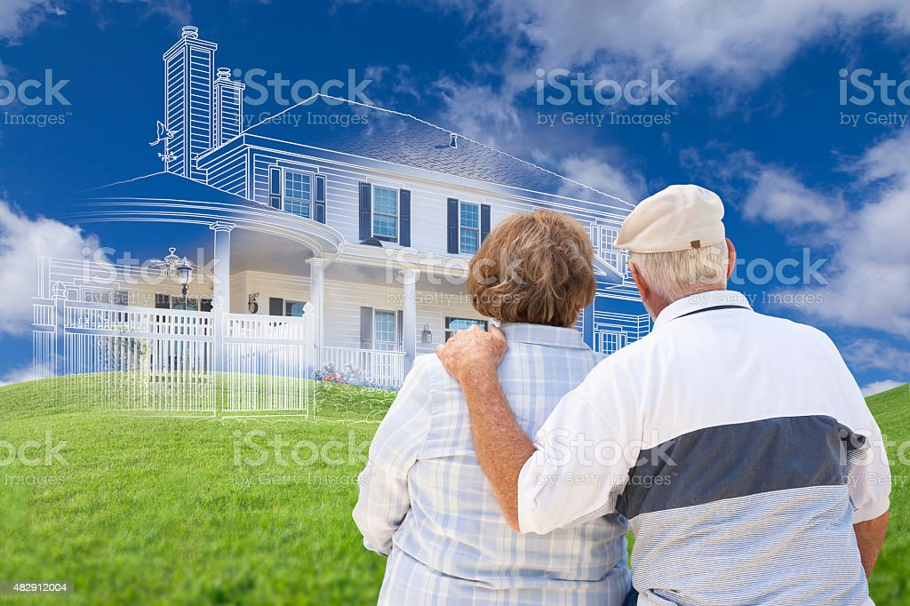 Senior Couple Faces Ghosted House Drawing, Green Grass Hill Behi stock photo