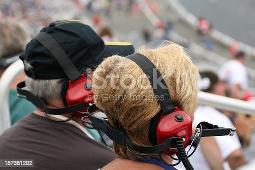 173015172 istock photo Senior Couple Fans Wearing Earmuffs at Racing Event 157381202