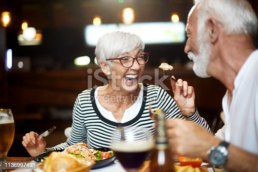 Elderly couple cheerfully feeding each other during a meal in a restaurant.