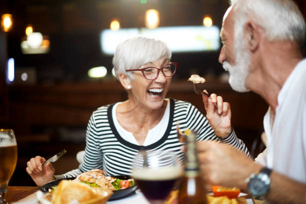 senior paar voeden elkaar en met een goede tijd tijdens een maaltijd in een restaurant - avondmaaltijd stockfoto's en -beelden