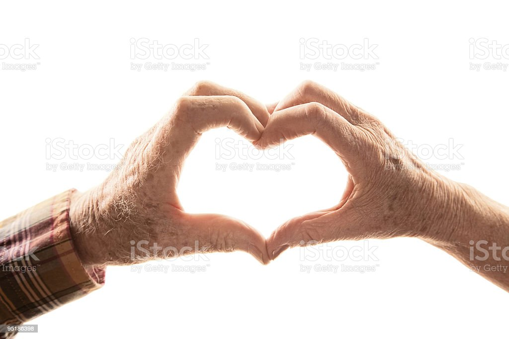 Senior couple forming heart with hands stock photo