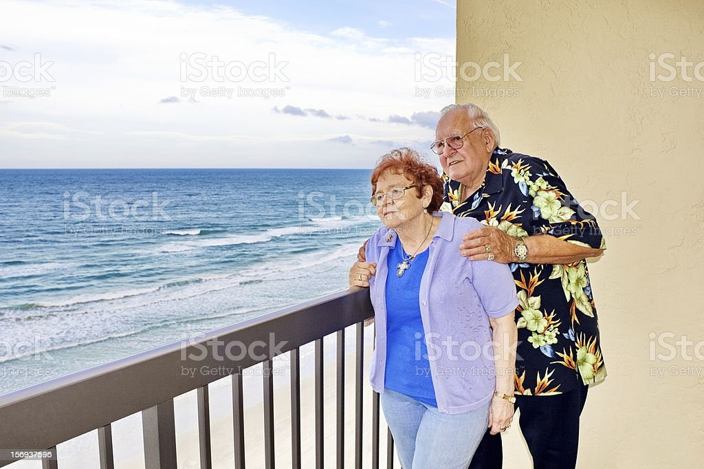 Senior Couple Gazing at Ocean from Balcony royalty-free stock photo