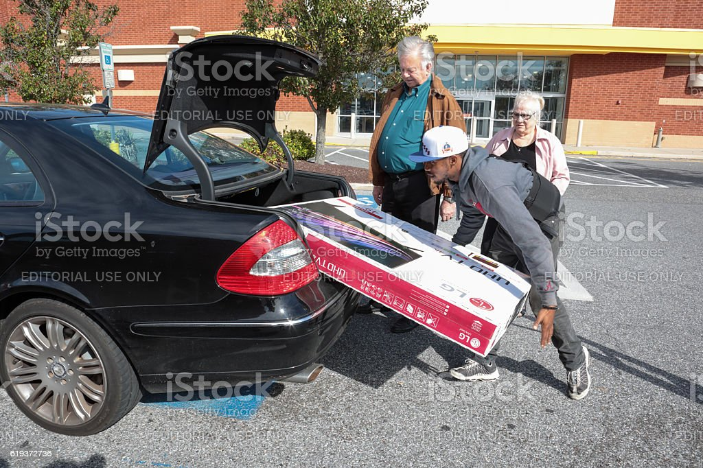 Senior couple gets help at store loading television into car stock photo
