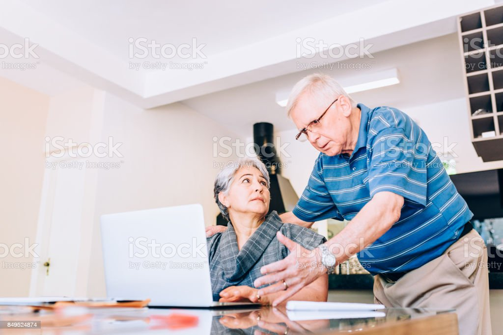 Senior couple getting bad news on computer stock photo