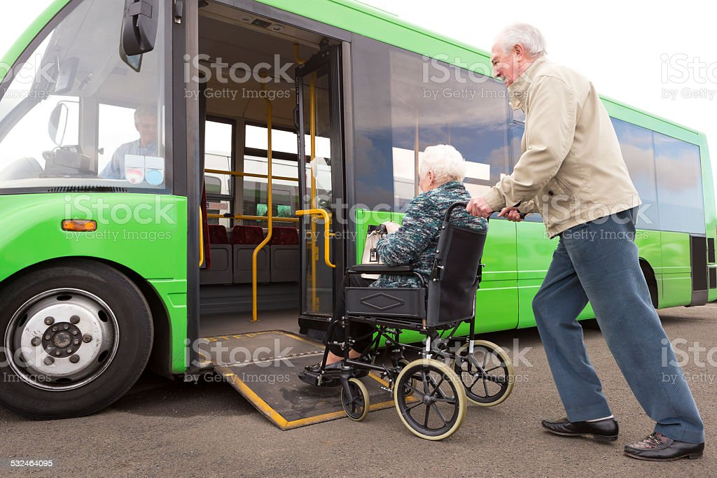 Senior Couple Getting on Bus Via Wheelchair Ramp stock photo