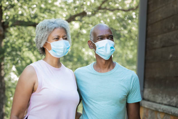 Senior couple go for walk together in public park while wearing masks stock photo