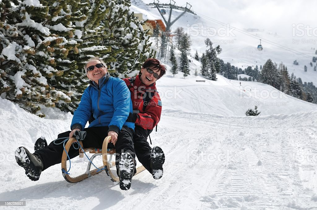 Senior couple going down on hill on a sledge while smiling stock photo