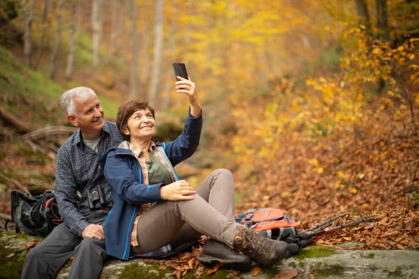 Senior couple going hiking in forest on mountain stock photo