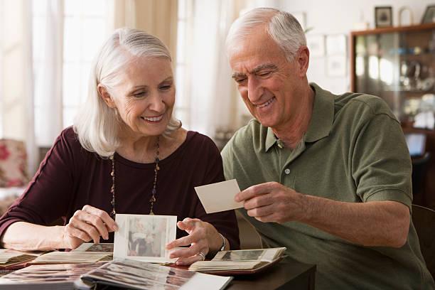 Senior couple going through photo album stock photo