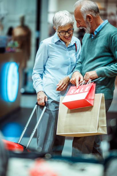 älteres paar, die gerne auf die dinge zeigen kauften sie nach einem einkaufsbummel in einer shopping mall - trolley kaufen stock-fotos und bilder