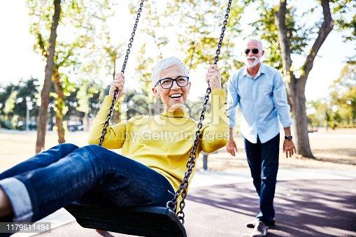 active senior couple enjoying  a swing in park
