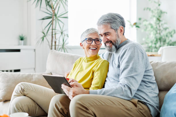 senior couple happy tablet computer love together portrait of happy smiling senior couple using tablet at home eastern europe stock pictures, royalty-free photos & images