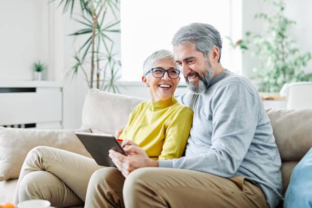 pareja mayor feliz tableta ordenador amor juntos - couple fotografías e imágenes de stock